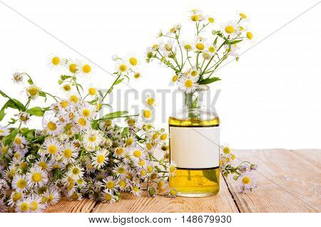 Alternative Medicine Concept - Bottle With Camomile On Wooden Table