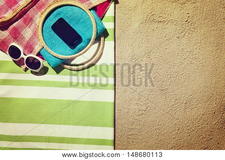 Top view of sandy beach with summer accessories and smartphone or tablet