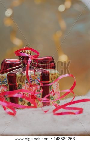 Close up of decorative Christmas decoration at a gift box with red ribbons on a gold blurred background. Selective focus on the box. Vertical