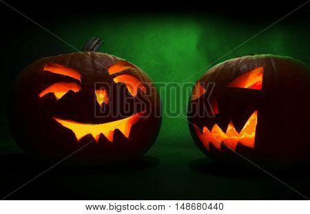 Two Carved Faces Of Pumpkins Glowing On Halloween On Green Background