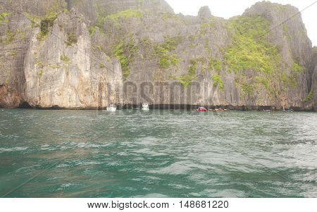 Boats moored off the cliffs of the Phi Phi Islands in Andaman Sea Thailand on Christmas day in the tropics.