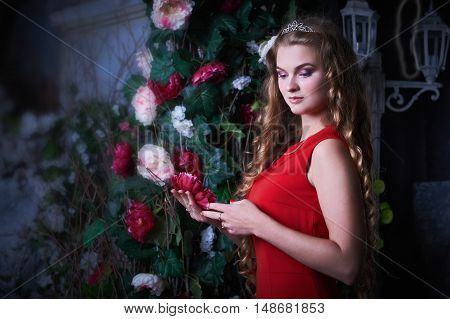 Beautiful princess in red dress sitting in a mystical garden