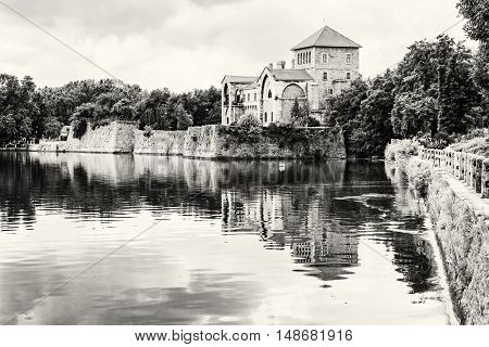 Beautiful castle in Tata Hungary. Travel destination. Architectural theme. Beautiful place. Black and white photo. Fortress is reflected in the lake.