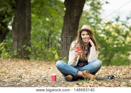Young millennial blonde woman with smart phone in park in autumn. Cool casual teenage girl with cellphone, takeaway coffee and analogue camera outdoors in fall. No retouch, natural light.