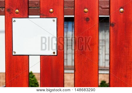 Red wooden fence with empty number plate