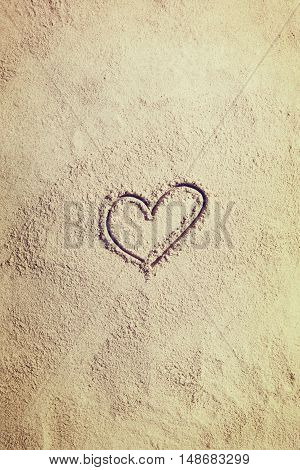 Top view of sandy beach with heart shape sign