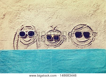 Top view of sandy beach with smiling family faces and towel