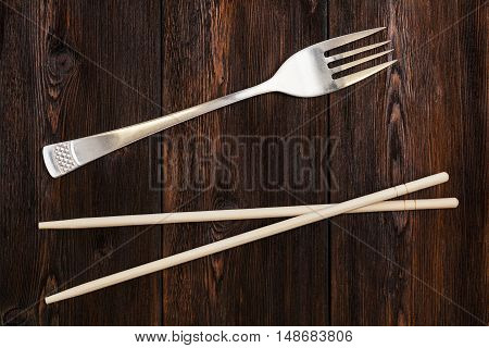 Wooden pairs of chopsticks vs fork on table. Abstract conceptual image