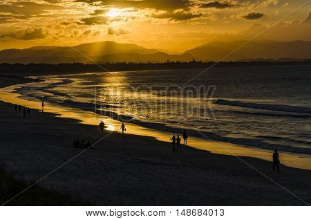 People at the beach of Byron Bay during sunset.