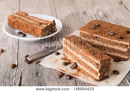 Pieces of chocolate cake on parchment paper and on a white plate on a gray wooden table.