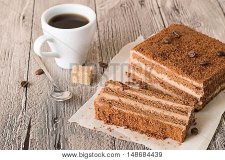 Pieces of chocolate cake on parchment paper, cup of coffee and spoon on a gray wooden table.
