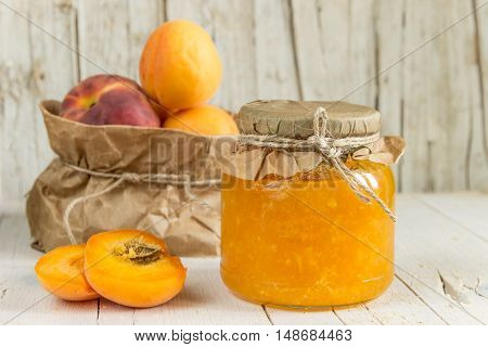 Jam from apricots and peaches and a few ripe fruits on wooden background