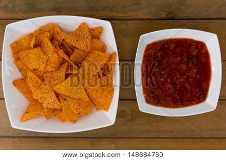 Nacho and salsa sauce in bowls on a wooden table