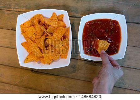 Hand dipping a nacho on salsa sauce