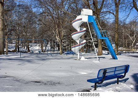 Blue and white playground equipment after a snowstorm
