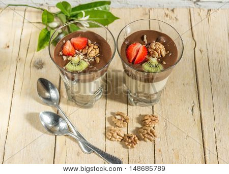 Chocolate Vanilla pudding with strawberries kiwi and walnuts in a glass on a wooden background