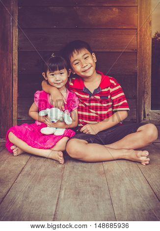 Asian brother put one's arm around sister's shoulder and smiling happy together. Concept about loving and bonding of sibling. Happy family spending time together. Vintage tone effect.