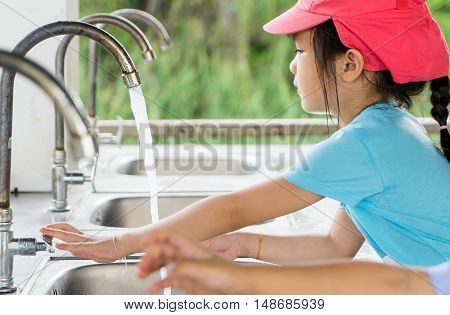Asian girl is watching her hand with clean water