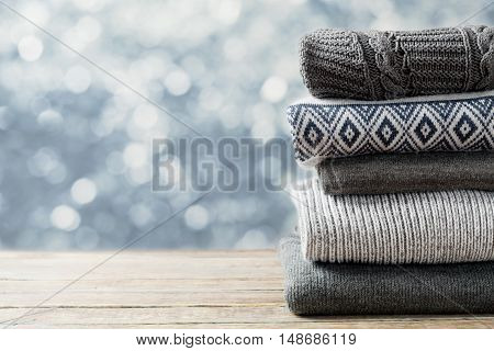 Pile of knitted winter and autumn clothes on wooden background, sweaters, knitwear, space for text.
