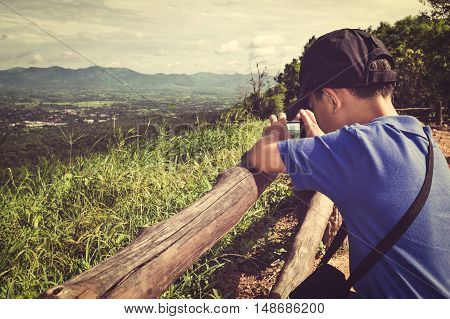 Side view of asian boy with camera at park. Child photographing views mountain against blue sky background. Child relaxing outdoors at the daytime travel on vacation. Vintage effect and cream tone.