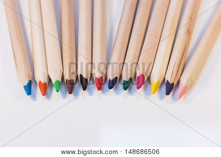 Crayons coming together in a lineup, on a white background
