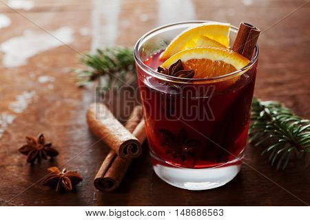 Christmas mulled wine or gluhwein with spices and orange slices on rustic table, traditional drink on winter holiday, magic light, selective focus.