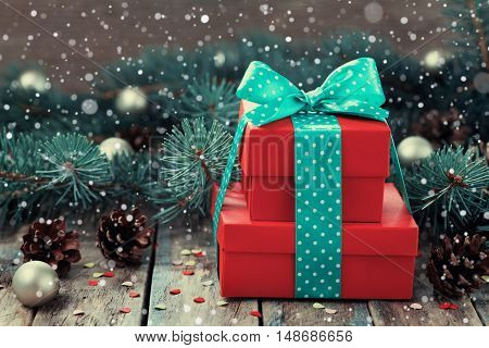Red present box with bow, ribbon, decoration of fir tree and conifer cone with magic snow effect. Christmas or New Year background. Vintage toned.