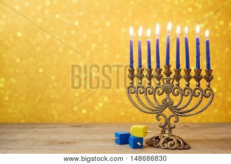 Jewish holiday Hanukkah background with vintage menorah and spinning top dreidel over lights bokeh.