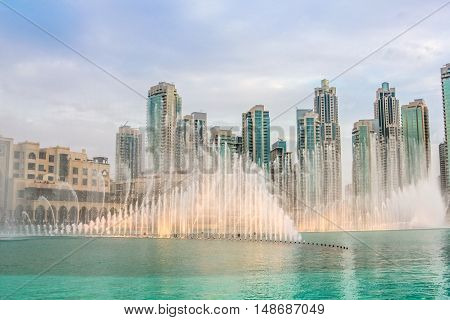 The Dubai Fountain, the world largest choreographed fountain on Burj Khalifa Lake, performs to the beat of the selected music at sunset. On background, skyscrapers of Old Town Island near Dubai Mall.