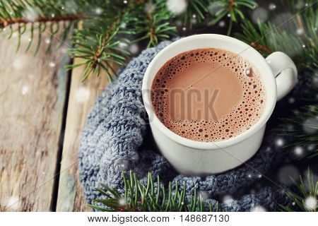Cup of hot cocoa or hot chocolate on knitted background with fir tree and cinnamon sticks, traditional beverage for winter time.