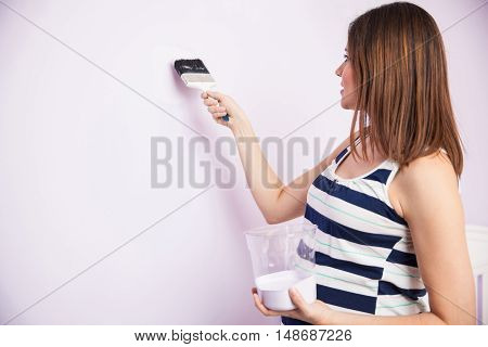 Young Pregnant Woman Painting A Room
