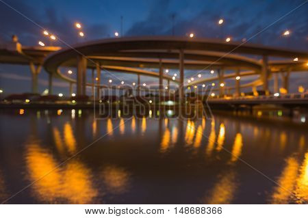Abstract blurred light highway road interchanged river front at twilight