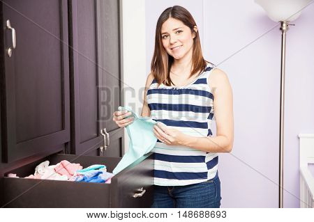 Pregnant Woman Folding Baby Clothes