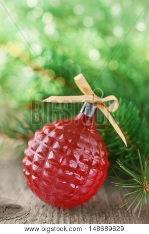 Christmas or New Year decorations with red ball and fir branches on wooden background with magic bokeh effect, selective focus.