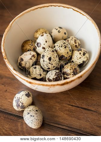 Quail eggs in a bowl on a wooden table, selective focus