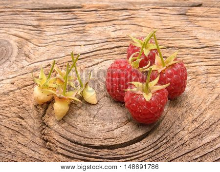 Ripe fresh raspberries on a wooden background