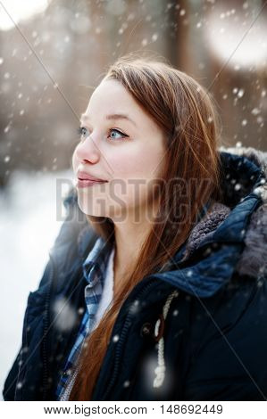 Headshot Of Young Woman Standing Under Snowfall