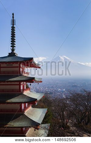 Mt. Fuji viewed from behind red Chureito Pagoda with clear blue sky background, Japan