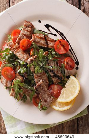 Warm Salad Of Grilled Beef With Arugula And Tomatoes Close-up. Vertical Top View