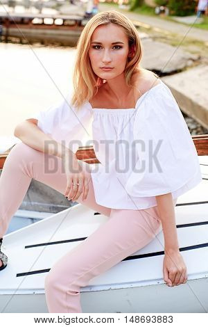 model tests of fashion blond girl in shirt posing in the boat in the dock by the sea