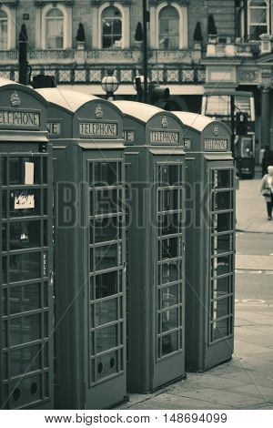 Telephone box in street with historical architecture in London in black and white.