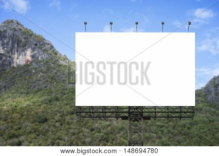 Blank big billboard against green mountain and blue sky background, for your advertising, put your own text here, isolate white on board