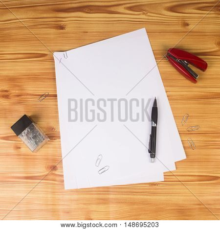 Blank paper and some office supplies are on wooden office table.