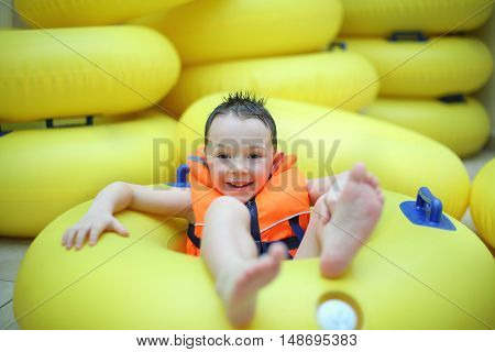 Happy little boy in a life jacket sitting in a big yellow swimming circle