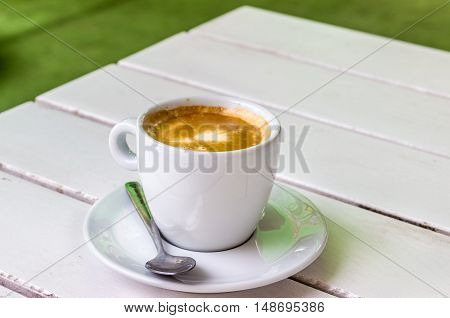 A cup of cappuccino on a white table in a cafe.