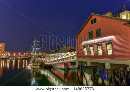 Boston, Massachusetts - September 5, 2016: The Boston Tea Party Museum in Boston Harbor in Massachusetts USA with its mix of modern and historic architecture at night.
