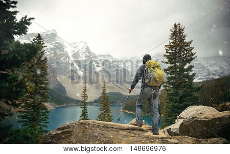 Hiker in wild with snow mountain and lake in national park