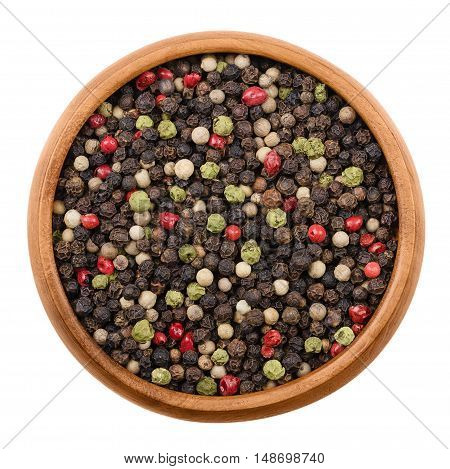 Mixed peppercorns in a wooden bowl on white background. Black, green, white and pink pepper. Dried seeds of Piper nigrum and Schinus molle, a spice, used  as seasoning. Isolated macro photo close up.