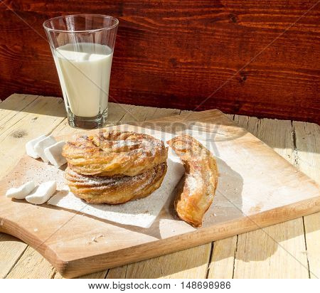 Freshly made churros with powdered sugar on a wooden background. Traditional Spanish cuisine dessert.