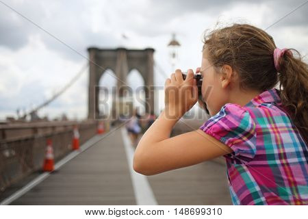 Girl takes pictures on the Brooklyn Bridge, side view